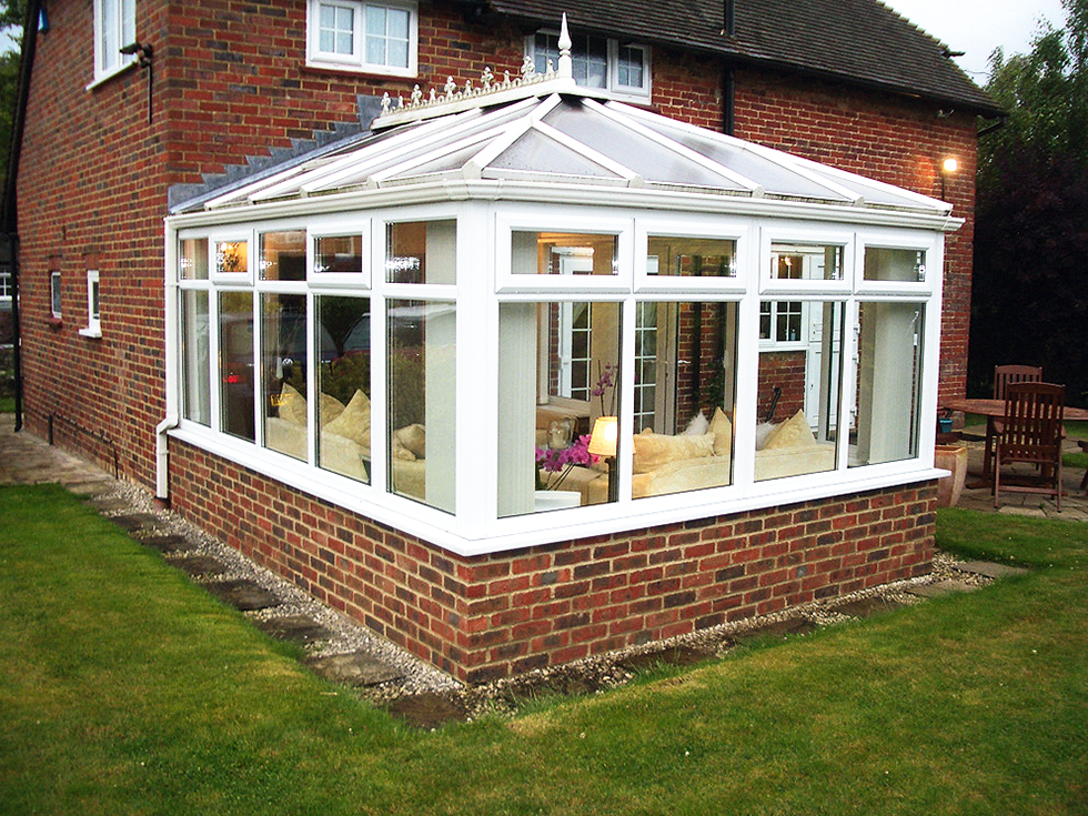 a dated uPVC conservatory with brick base