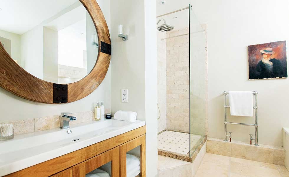 bathroom in a basement with wooden vanity unit and wooden mirror and walk-in shower