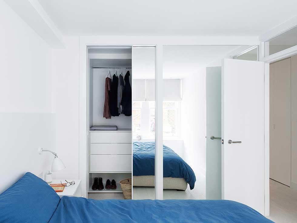 London flat white bedroom blue bedding bespoke walk in wardrobe