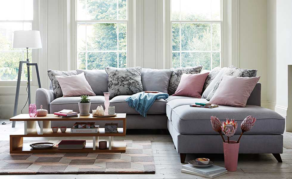 living room cushions. mixed pastel trend in living room with slouchy corner sofa and pink cushions
