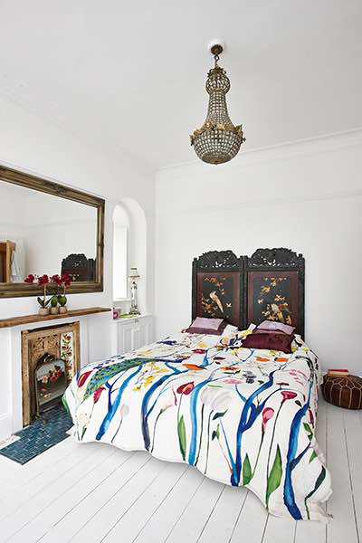 colourful floral bed spread in a simple traditional bedroom