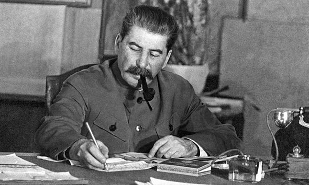 Joseph Stalin sitting at a desk writing on documents, pipe in mouth