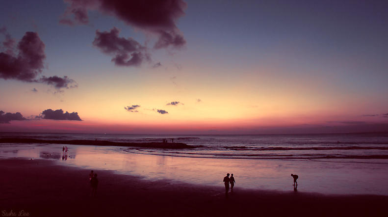 a beautiful beach in kuta, bali, indonesia at sunset. a beautiful orange and blue sunset on the beach at twilight.