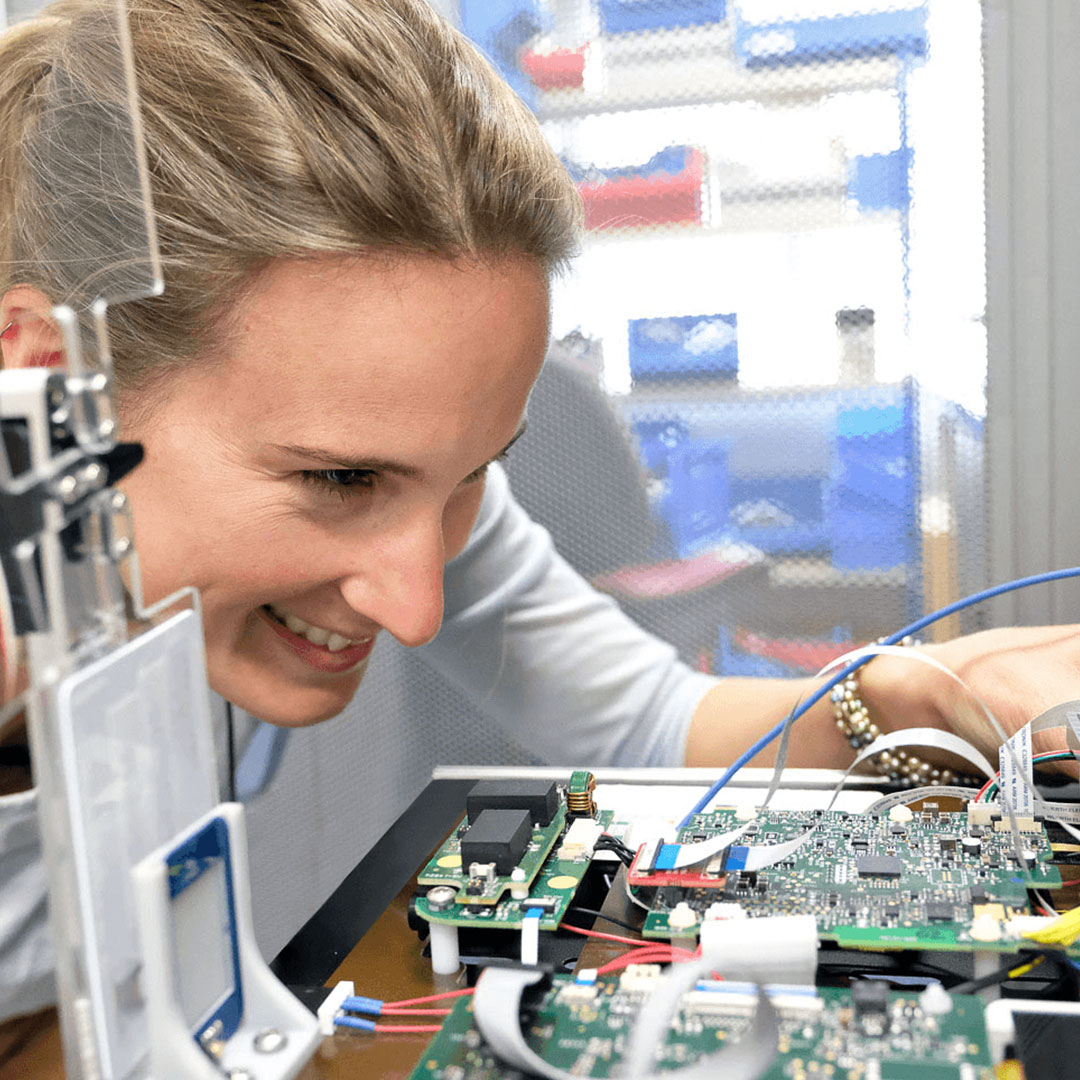 A woman smiling whilst conducting some point of care diagnostics integration testing