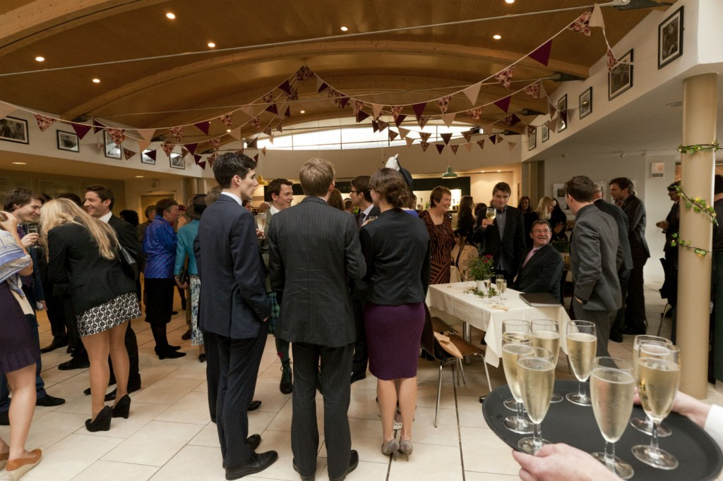 People gathered in the Greene Room bar with glasses of Champagne being served
