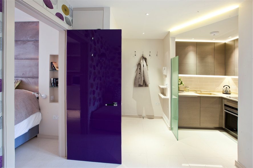 8-aubergine-color-lacquer-door-to-bedroom-from-living-area-entryway-and-kitchen-beyond
