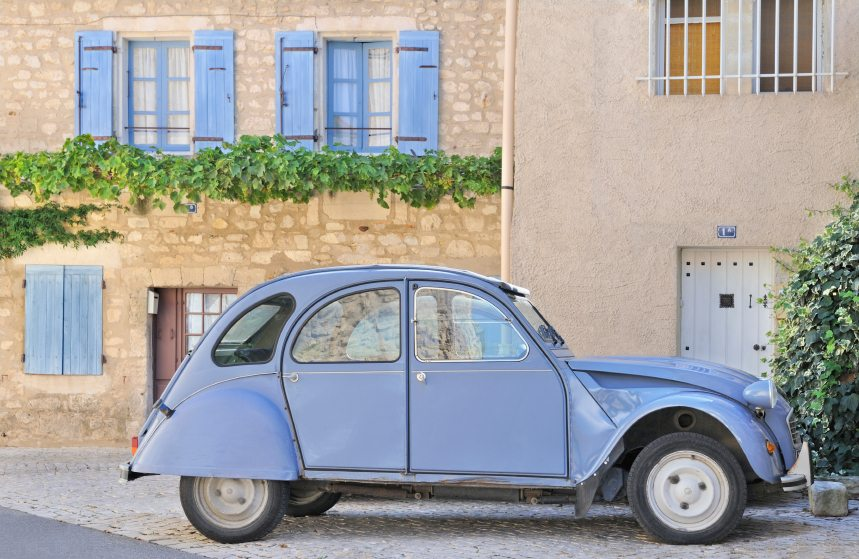 Classic french provincial village scene featuring blue citroen car and old buildings with shutters