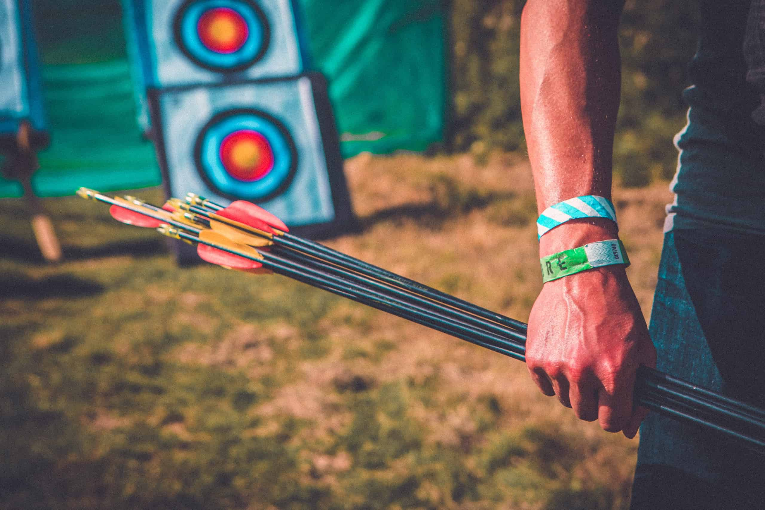 Close up of arrows at the archery activity at Camp Wildfire. A summer weekend break in a forest near London and Kent. An outdoor woodland retreat featuring adventure activities, live music, DJs, parties and camping. Half summer adventure activity camp, half music festival, for adults only.