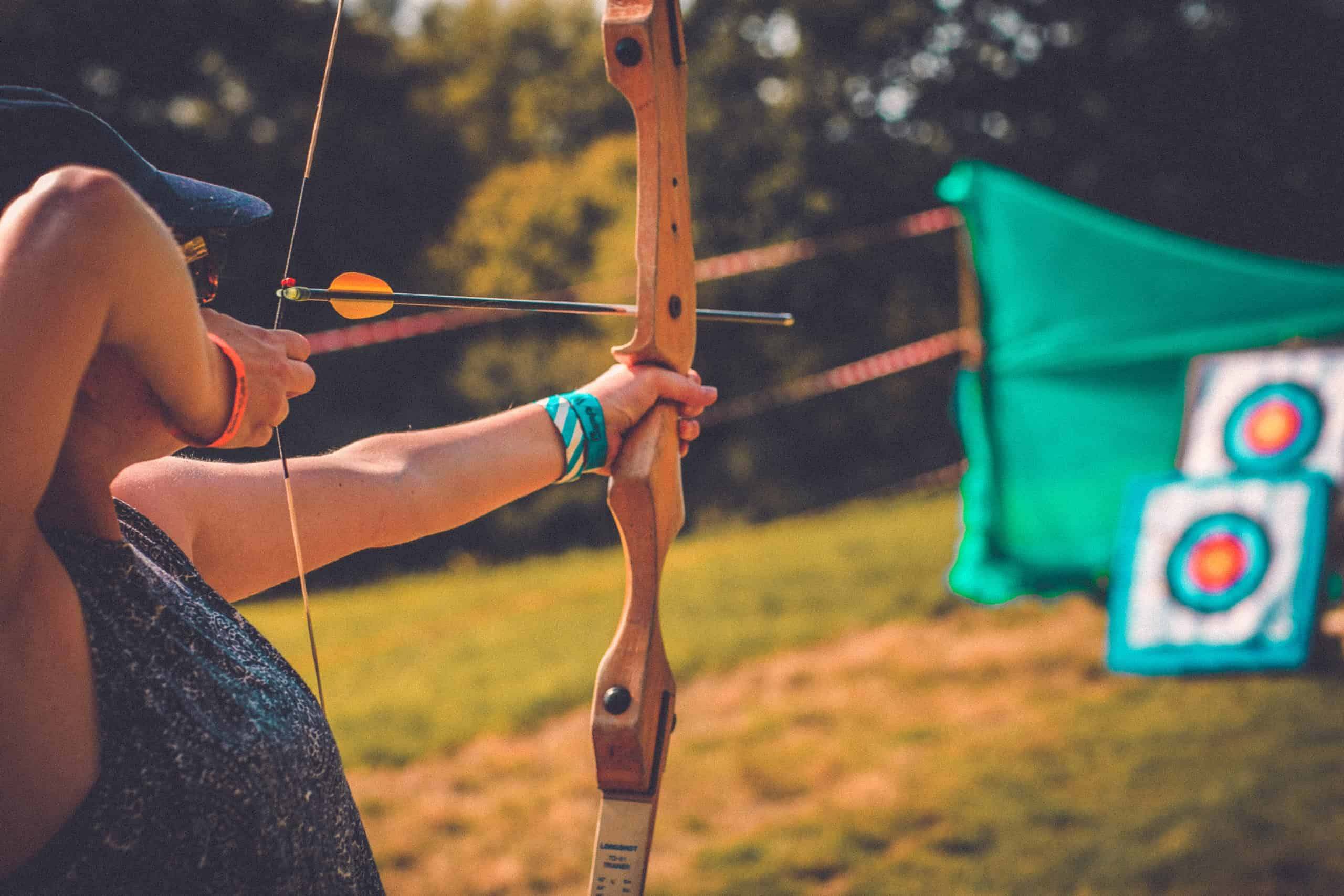 Bow and arrow at the archery activity at Camp Wildfire. A summer weekend break in a forest near London and Kent. An outdoor woodland retreat featuring adventure activities, live music, DJs, parties and camping. Half summer adventure activity camp, half music festival, for adults only.
