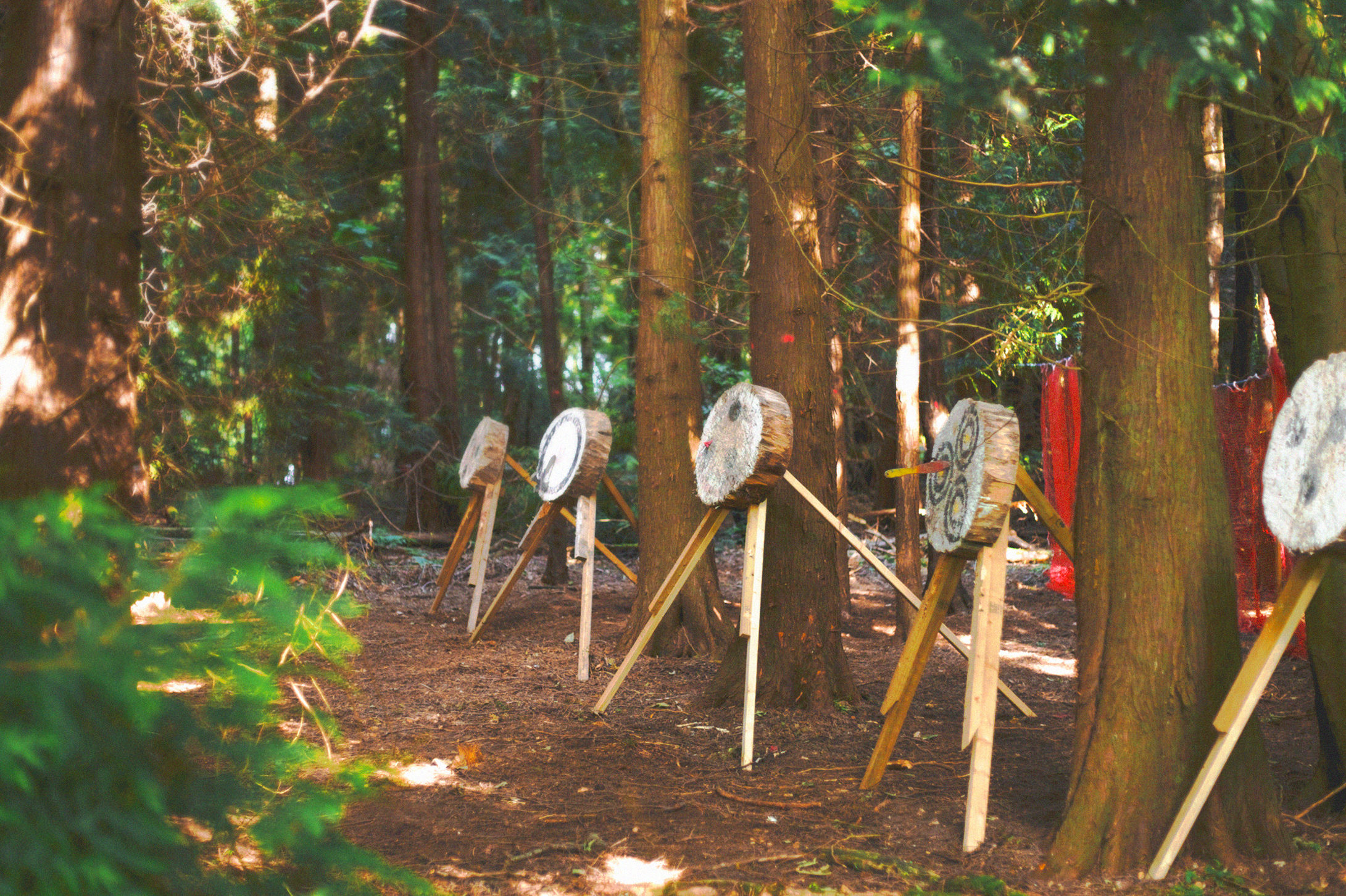 Archery targets at the archery range at Camp Wildfire. A summer weekend break in a forest near London and Kent. An outdoor woodland retreat featuring adventure activities, live music, DJs, parties and camping. Half summer adventure activity camp, half music festival, for adults only.