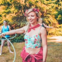 Girl at the hula hoop activity at Camp Wildfire. A summer weekend break in a forest near London and Kent. An outdoor woodland retreat featuring adventure activities, live music, DJs, parties and camping. Half summer adventure activity camp, half music festival, for adults only.