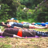 People lying down at the meditation activity at Camp Wildfire. A summer weekend break in a forest near London and Kent. An outdoor woodland retreat featuring adventure activities, live music, DJs, parties and camping. Half summer adventure activity camp, half music festival, for adults only.