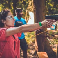 Girl at the pistol shooting activity at Camp Wildfire. A summer weekend break in a forest near London and Kent. An outdoor woodland retreat featuring adventure activities, live music, DJs, parties and camping. Half summer adventure activity camp, half music festival, for adults only.