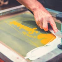 Close up of screen printing at Camp Wildfire. A summer weekend break in a forest near London and Kent. An outdoor woodland retreat featuring adventure activities, live music, DJs, parties and camping. Half summer adventure activity camp, half music festival, for adults only.