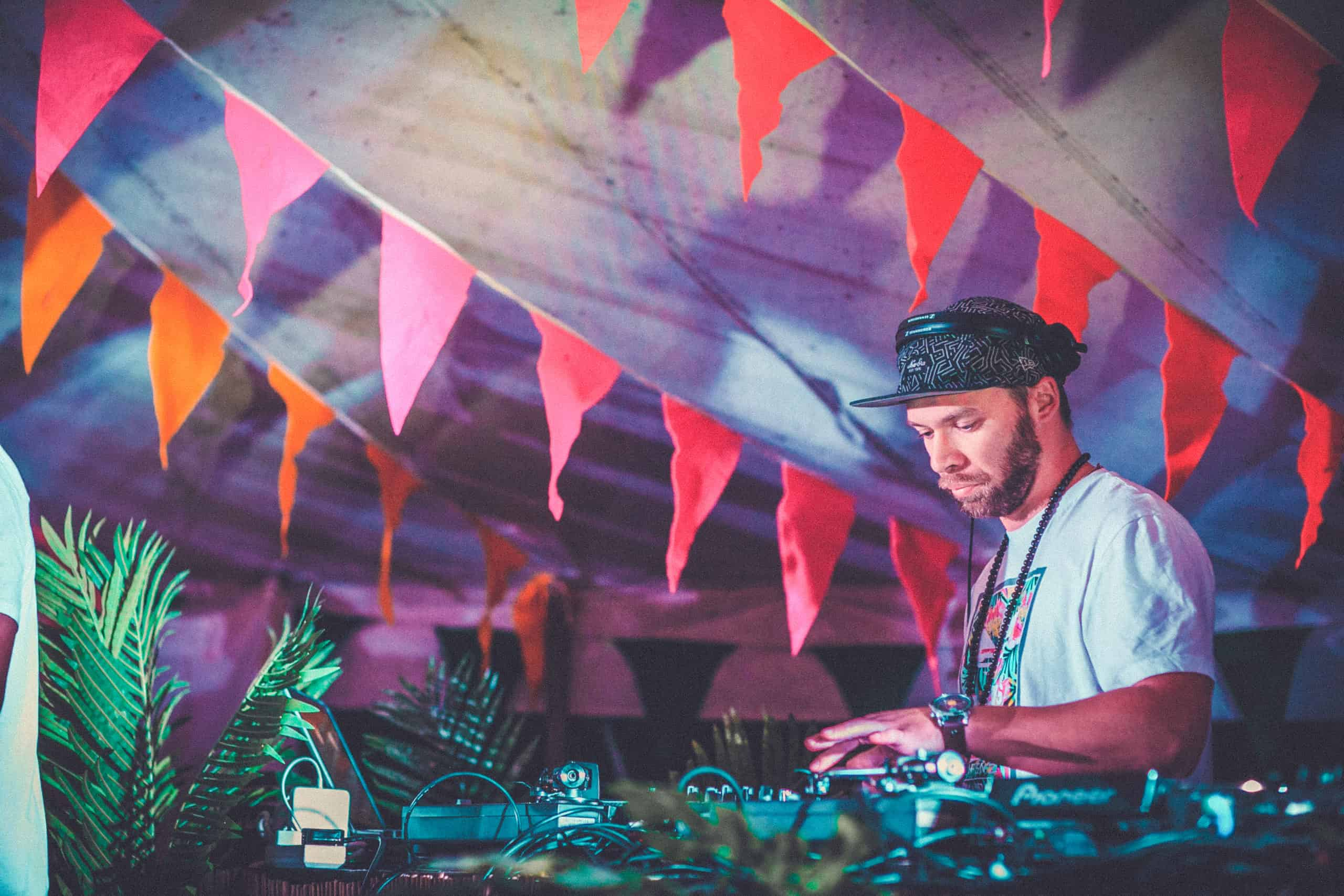 Shaka Loves You on the decks on stage at Camp Wildfire. A summer weekend break in a forest near London and Kent. An outdoor woodland retreat featuring adventure activities, live music, DJs, parties and camping. Half summer adventure activity camp, half music festival, for adults only.