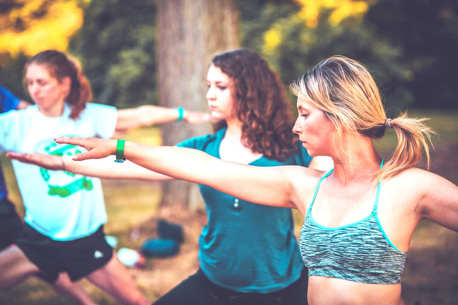 People practising yoga at Camp Wildfire. A summer weekend break in a forest near London and Kent. An outdoor woodland retreat featuring adventure activities, live music, DJs, parties and camping. Half summer adventure activity camp, half music festival, for adults only.