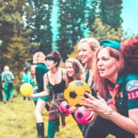 People playing dodgeball at Camp Wildfire. A summer weekend break in a forest near London and Kent. An outdoor woodland retreat featuring adventure activities, live music, DJs, parties and camping. Half summer adventure activity camp, half music festival, for adults only.
