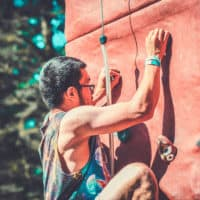 Man the climbing wall at Camp Wildfire. Peop A summer weekend break in a forest near London and Kent. An outdoor woodland retreat featuring adventure activities, live music, DJs, parties and camping. Half summer adventure activity camp, half music festival, for adults only.