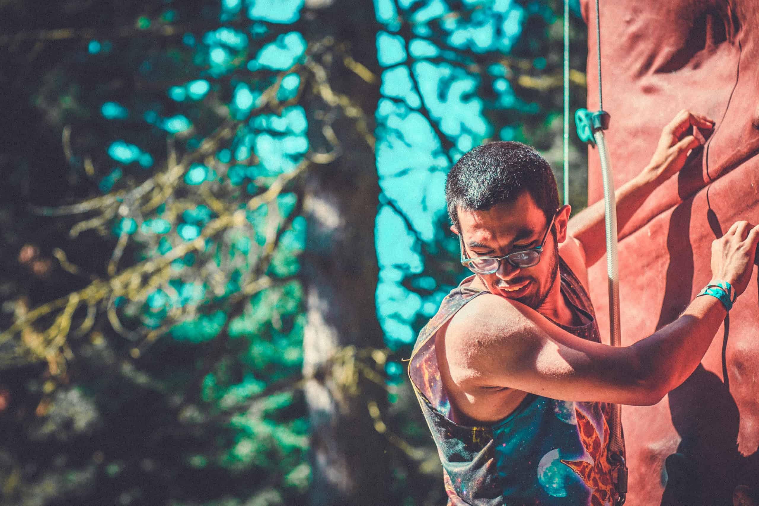 Man on climbing wall at Camp Wildfire. A summer weekend break in a forest near London and Kent. An outdoor woodland retreat featuring adventure activities, live music, DJs, parties and camping. Half summer adventure activity camp, half music festival, for adults only.