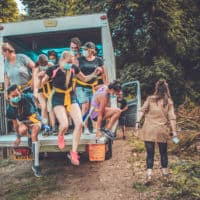 Group of people jumping from lorry on the zombie run activity. A summer weekend break in a forest near London and Kent. An outdoor woodland retreat featuring adventure activities, live music, DJs, parties and camping. Half summer adventure activity camp, half music festival, for adults only.