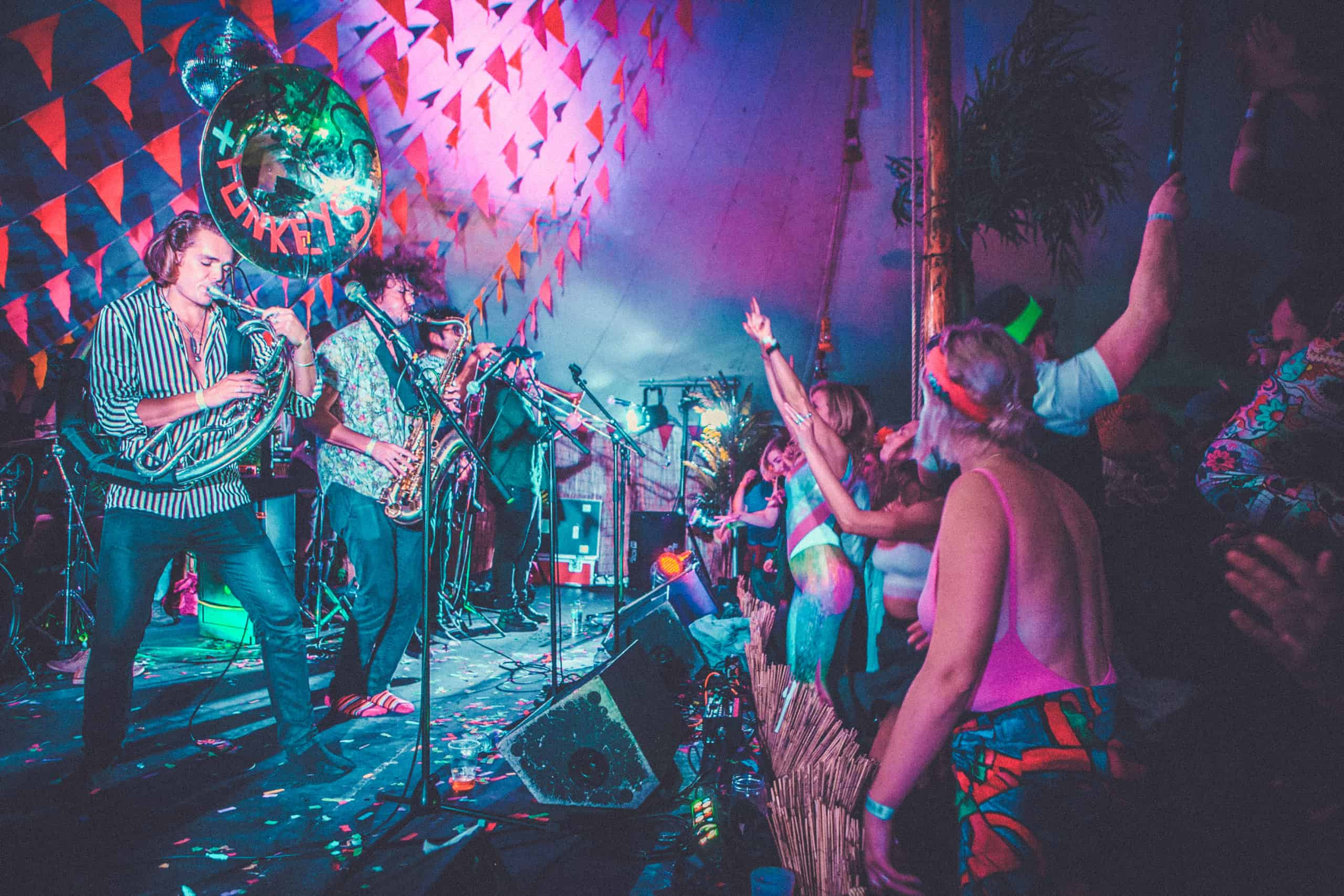 Brass Funkey's at Camp Wildfire on stage at the discotheque tent. A summer weekend break in a forest near London and Kent. An outdoor woodland retreat featuring adventure activities, live music, DJs, parties and camping. Half summer adventure activity camp, half music festival, for adults only.