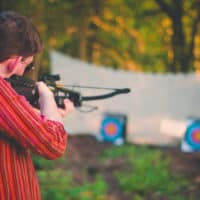 Man shooting crossbow at Camp Wildfire. A summer weekend break in a forest near London and Kent. An outdoor woodland retreat featuring adventure activities, live music, DJs, parties and camping. Half summer adventure activity camp, half music festival, for adults only.