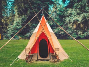 4 star tipi tent at Camp Wildfire. xA summer weekend break in a forest near London and Kent. An outdoor woodland retreat featuring adventure activities, live music, DJs, parties and camping. Half summer adventure activity camp, half music festival, for adults only.
