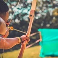 Man holding a bow and arrow in the archery activity at Camp Wildfire. A summer weekend break in a forest near London and Kent. An outdoor woodland retreat featuring adventure activities, live music, DJs, parties and camping. Half summer adventure activity camp, half music festival, for adults only.