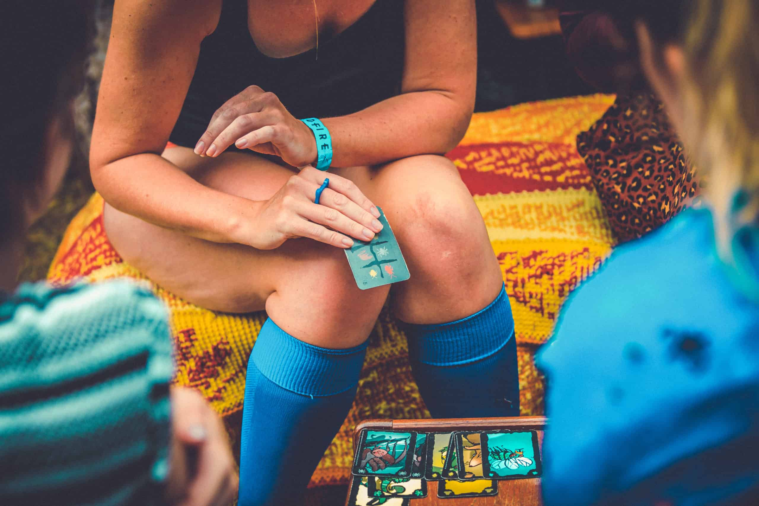 Girl playing a card games in her patrol socks. A summer weekend break in a forest near London and Kent. An outdoor woodland retreat featuring adventure activities, live music, DJs, parties and camping. Half summer adventure activity camp, half music festival, for adults only.