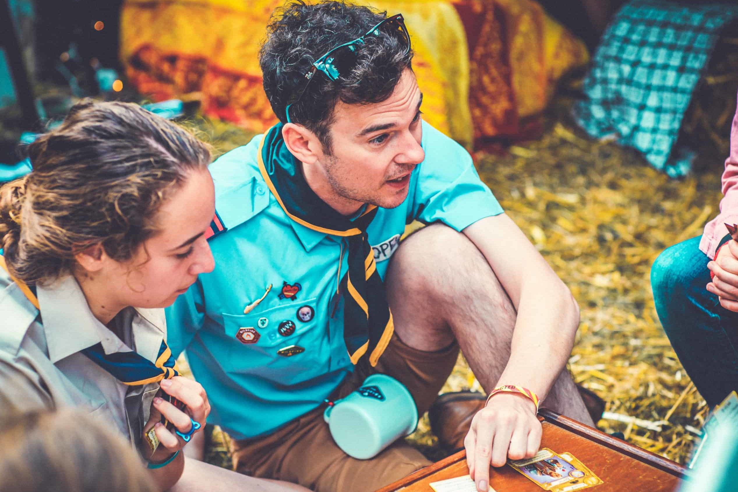 A guy in uniform with scout badges on sat playing a card game at Camp Wildfire. A summer weekend break in a forest near London and Kent. An outdoor woodland retreat featuring adventure activities, live music, DJs, parties and camping. Half summer adventure activity camp, half music festival, for adults only.