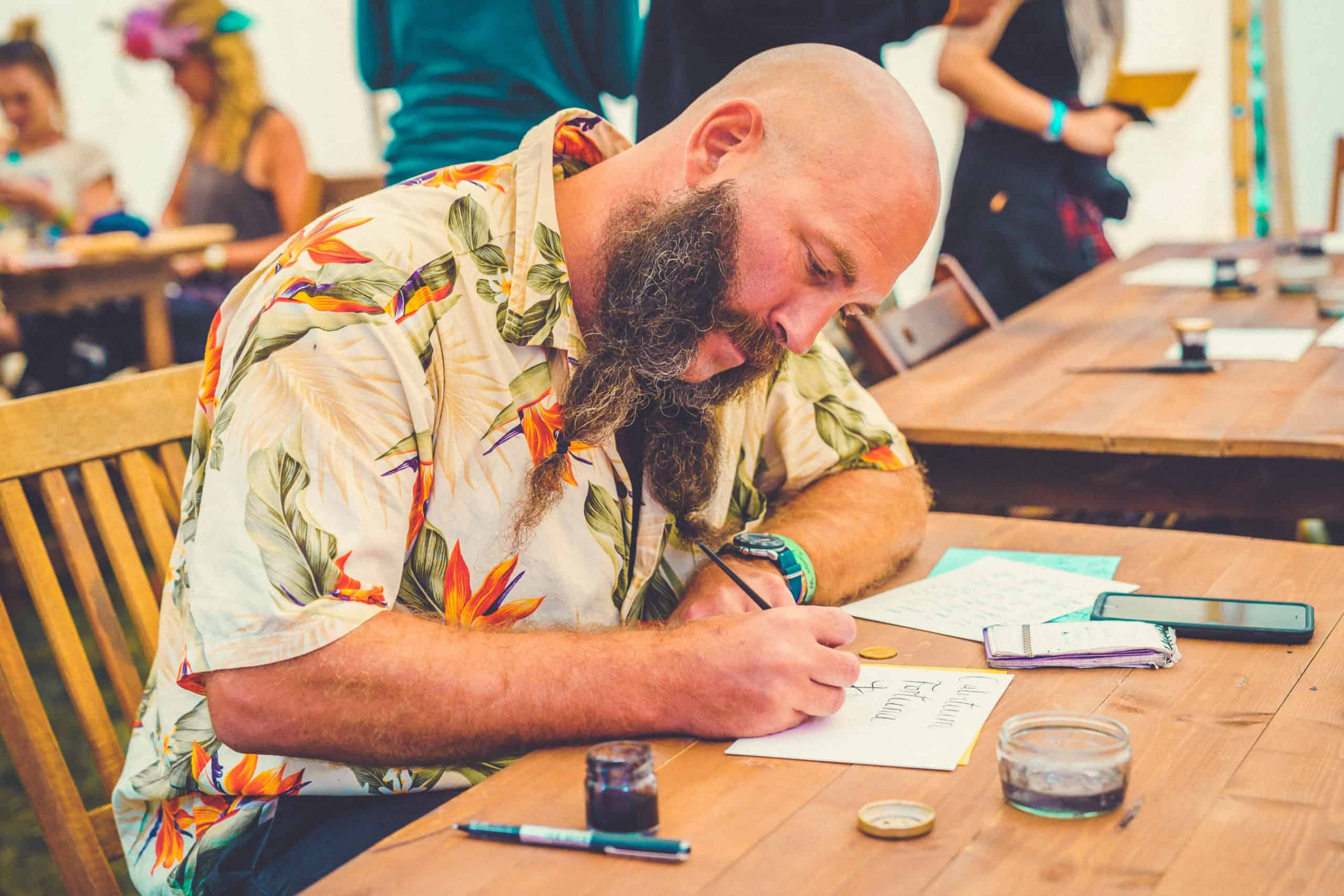 A bearded man in a floral shirt sat down at the calligraphy activity at Camp Wildfire. A summer weekend break in a forest near London and Kent. An outdoor woodland retreat featuring adventure activities, live music, DJs, parties and camping. Half summer adventure activity camp, half music festival, for adults only.
