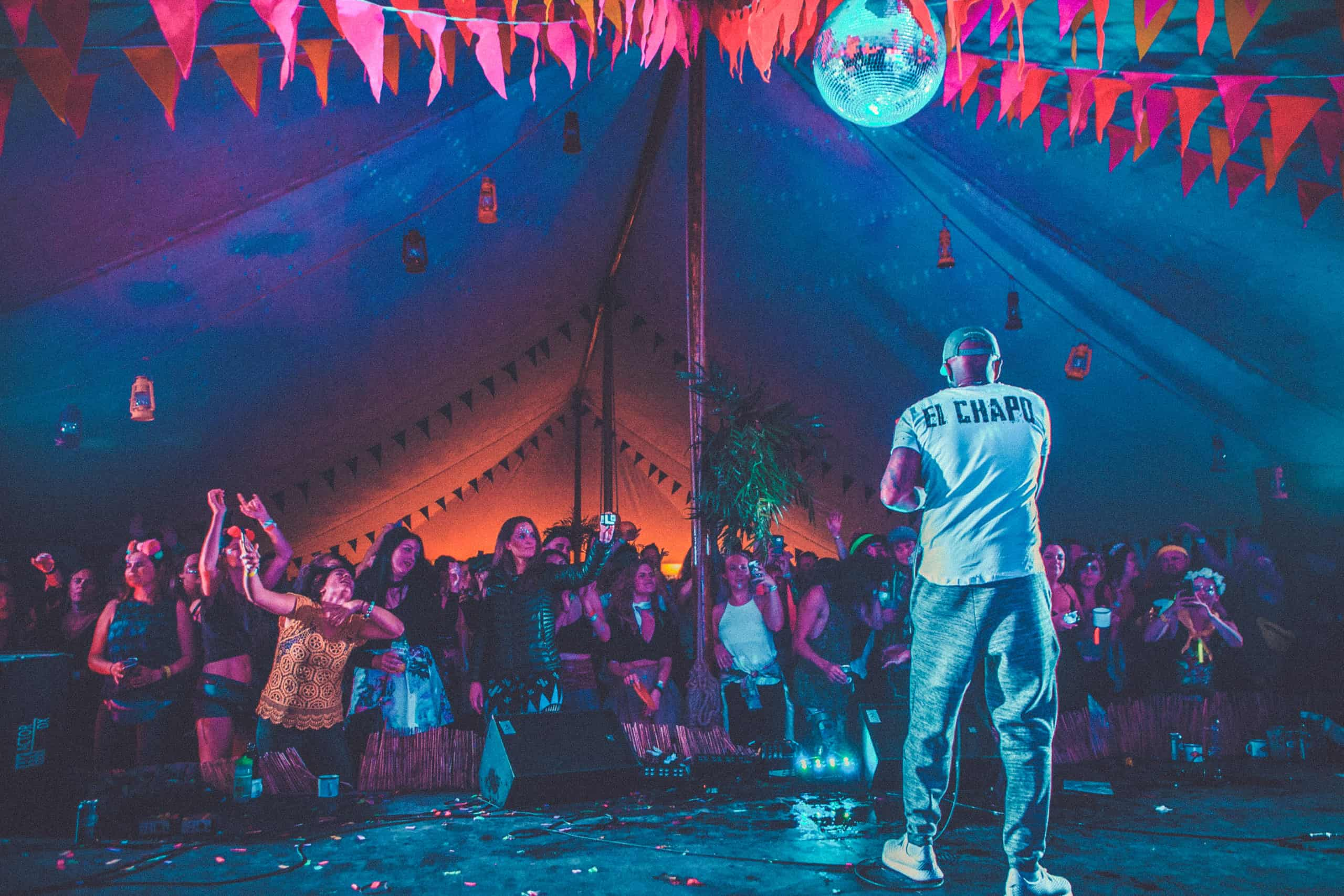 DJ Luck and MC Neat on stage at Camp Wildfire. A summer weekend break in a forest near London and Kent. An outdoor woodland retreat featuring adventure activities, live music, DJs, parties and camping. Half summer adventure activity camp, half music festival, for adults only.