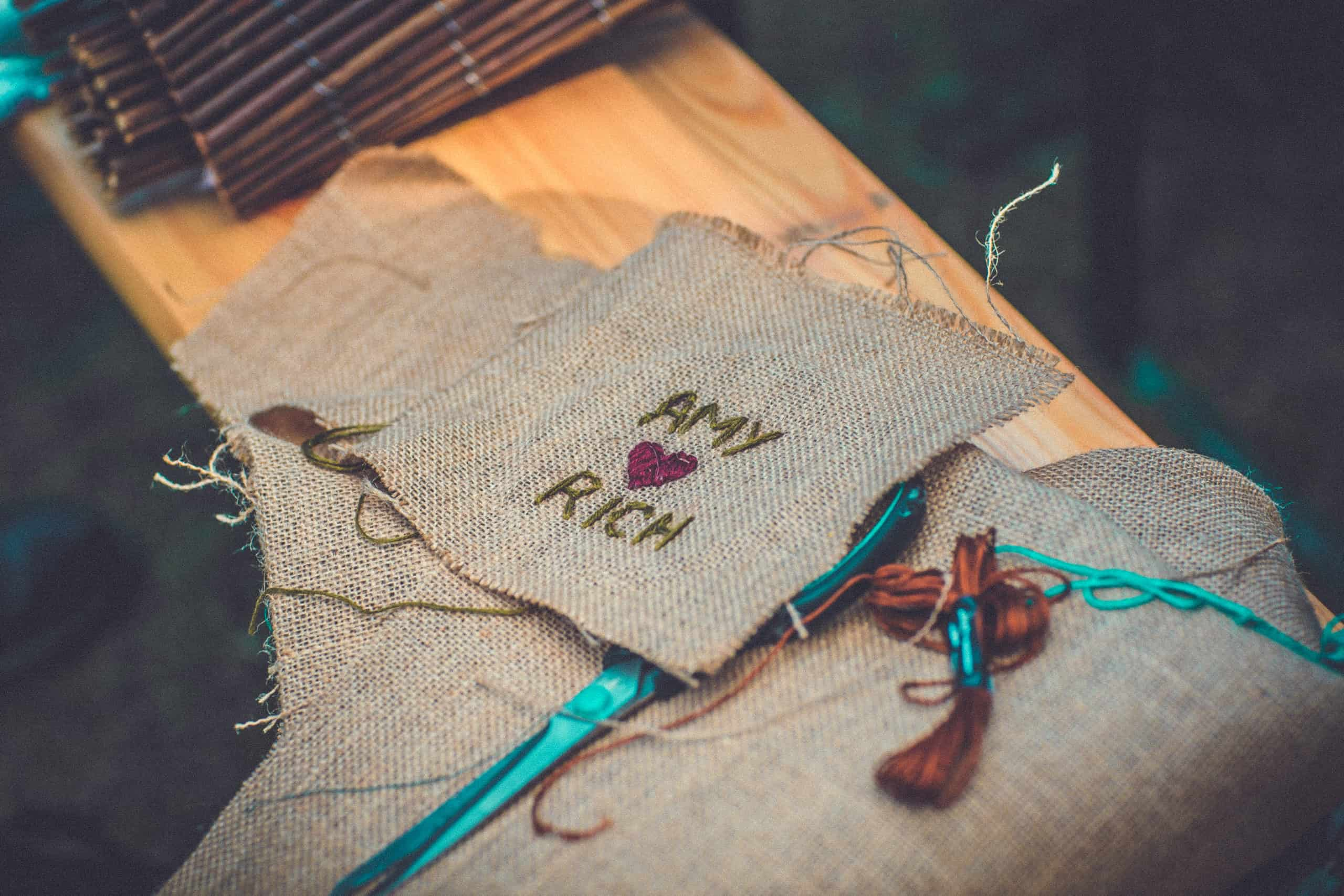Close up of crafted embroidery at Camp Wildfire. A summer weekend break in a forest near London and Kent. An outdoor woodland retreat featuring adventure activities, live music, DJs, parties and camping. Half summer adventure activity camp, half music festival, for adults only.