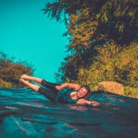Girl on the extreme water slide. A summer weekend break in a forest near London and Kent. An outdoor woodland retreat featuring adventure activities, live music, DJs, parties and camping. Half summer adventure activity camp, half music festival, for adults only.