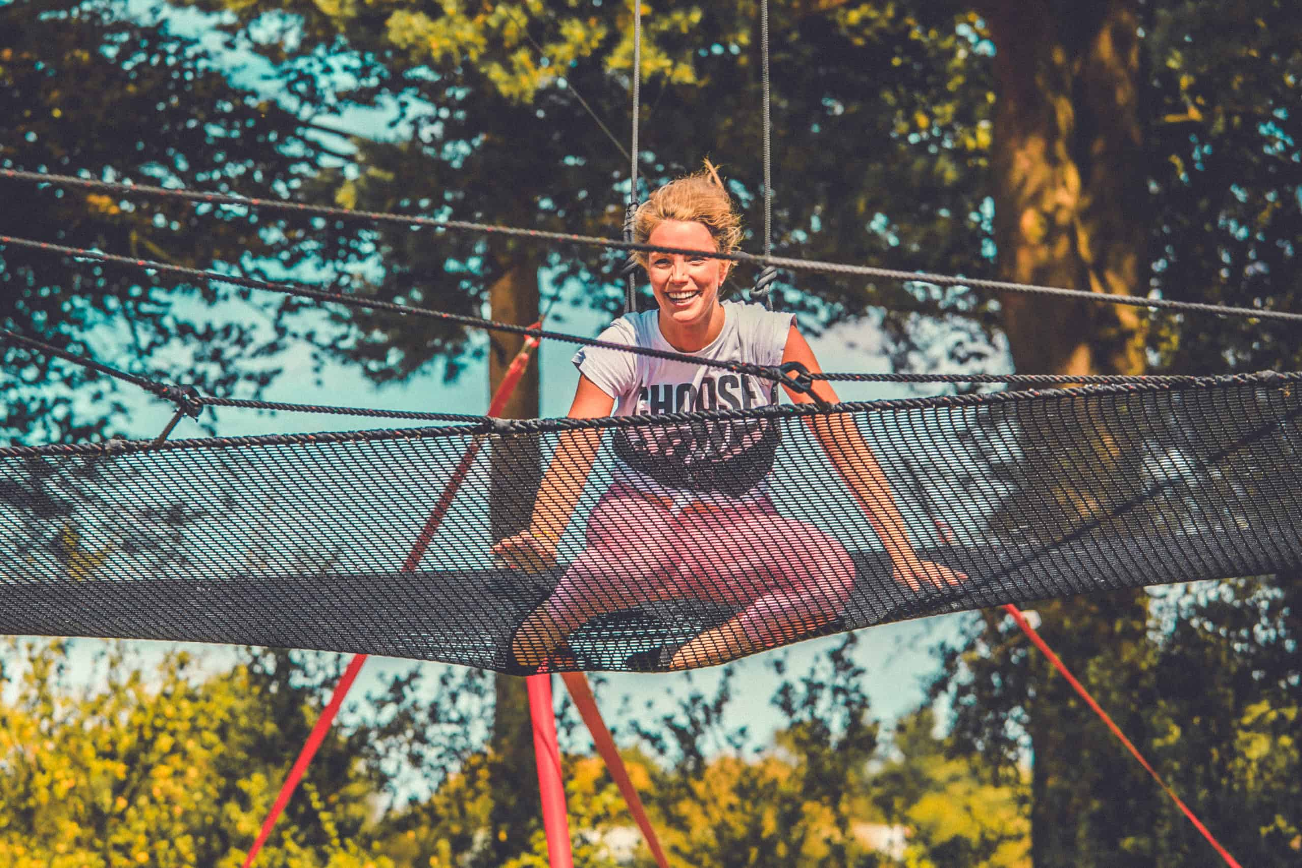 Girl with blonde hair smiling at the flying trapeze activity at Camp Wildfire. A summer weekend break in a forest near London and Kent. An outdoor woodland retreat featuring adventure activities, live music, DJs, parties and camping. Half summer adventure activity camp, half music festival, for adults only.
