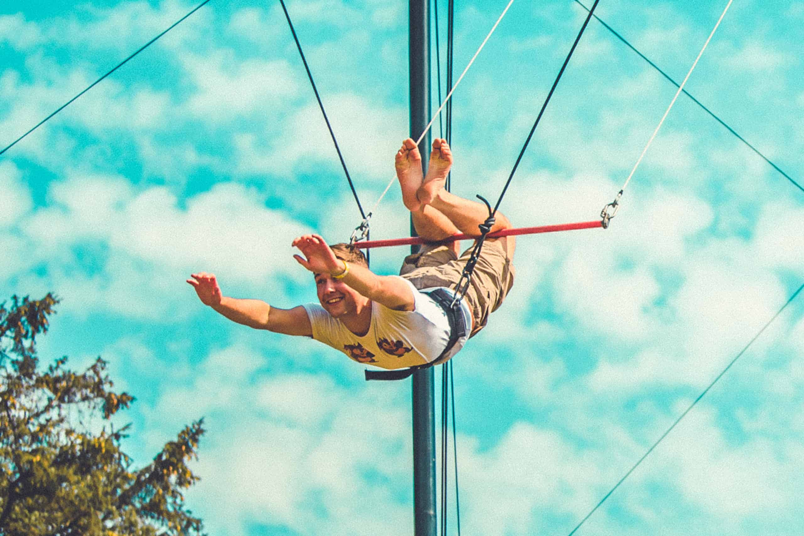 Man in the air on the flying trapeze at Camp Wildfire