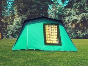 Holiday vintage camping tent. A summer weekend break in a forest near London and Kent. An outdoor woodland retreat featuring adventure activities, live music, DJs, parties and camping. Half summer adventure activity camp, half music festival, for adults only.