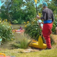 Kayaking activity at Camp Wildfire. A summer weekend break in a forest near London and Kent. An outdoor woodland retreat featuring adventure activities, live music, DJs, parties and camping. Half summer adventure activity camp, half music festival, for adults only.