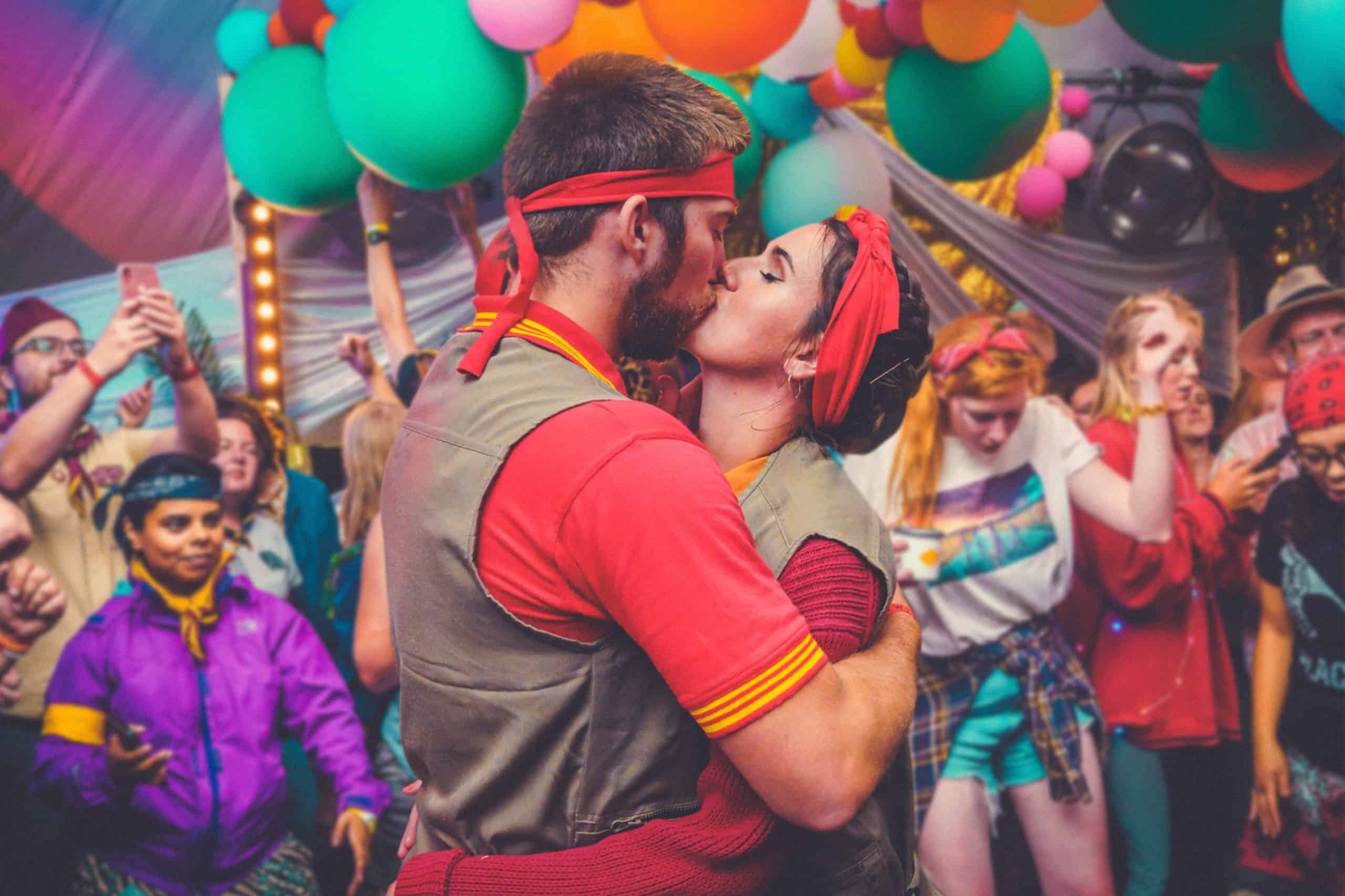 Couple having a romantic kiss whilst partying at Camp Wildfire. The UK's Best Alternative Festival. UK's Top Unique Event. A summer weekend break in a forest near London and Kent. An outdoor woodland retreat featuring adventure activities, live music, DJs, parties and camping. Half summer adventure activity camp, half music festival, for adults only.