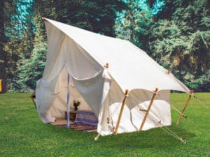 White mini safari style tent. A summer weekend break in a forest near London and Kent. An outdoor woodland retreat featuring adventure activities, live music, DJs, parties and camping. Half summer adventure activity camp, half music festival, for adults only.