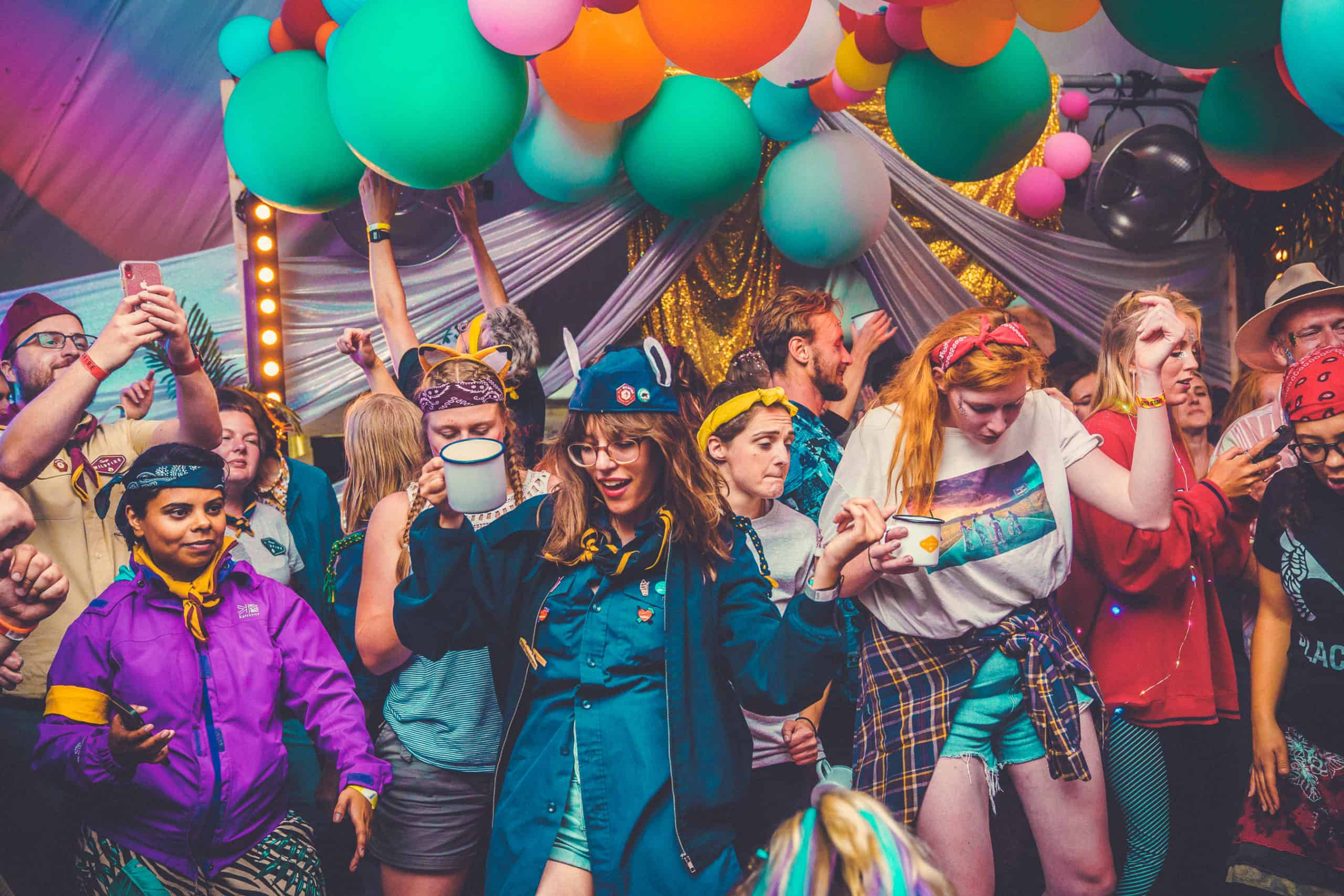 Lots of wild things partying underneath colourful balloons at Camp Wildfire. A summer weekend break in a forest near London and Kent. An outdoor woodland retreat featuring adventure activities, live music, DJs, parties and camping. Half summer adventure activity camp, half music festival, for adults only.