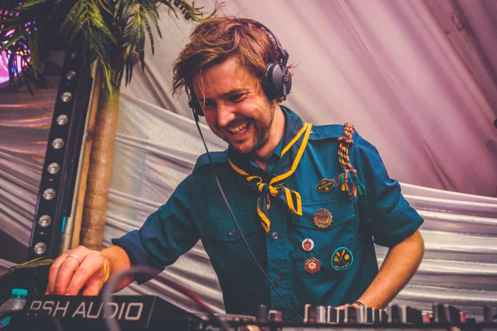 Lee in his patrol uniform on the decks in the discotheque tent at Camp Wildfire. A summer weekend break in a forest near London and Kent. An outdoor woodland retreat featuring adventure activities, live music, DJs, parties and camping. Half summer adventure activity camp, half music festival, for adults only.