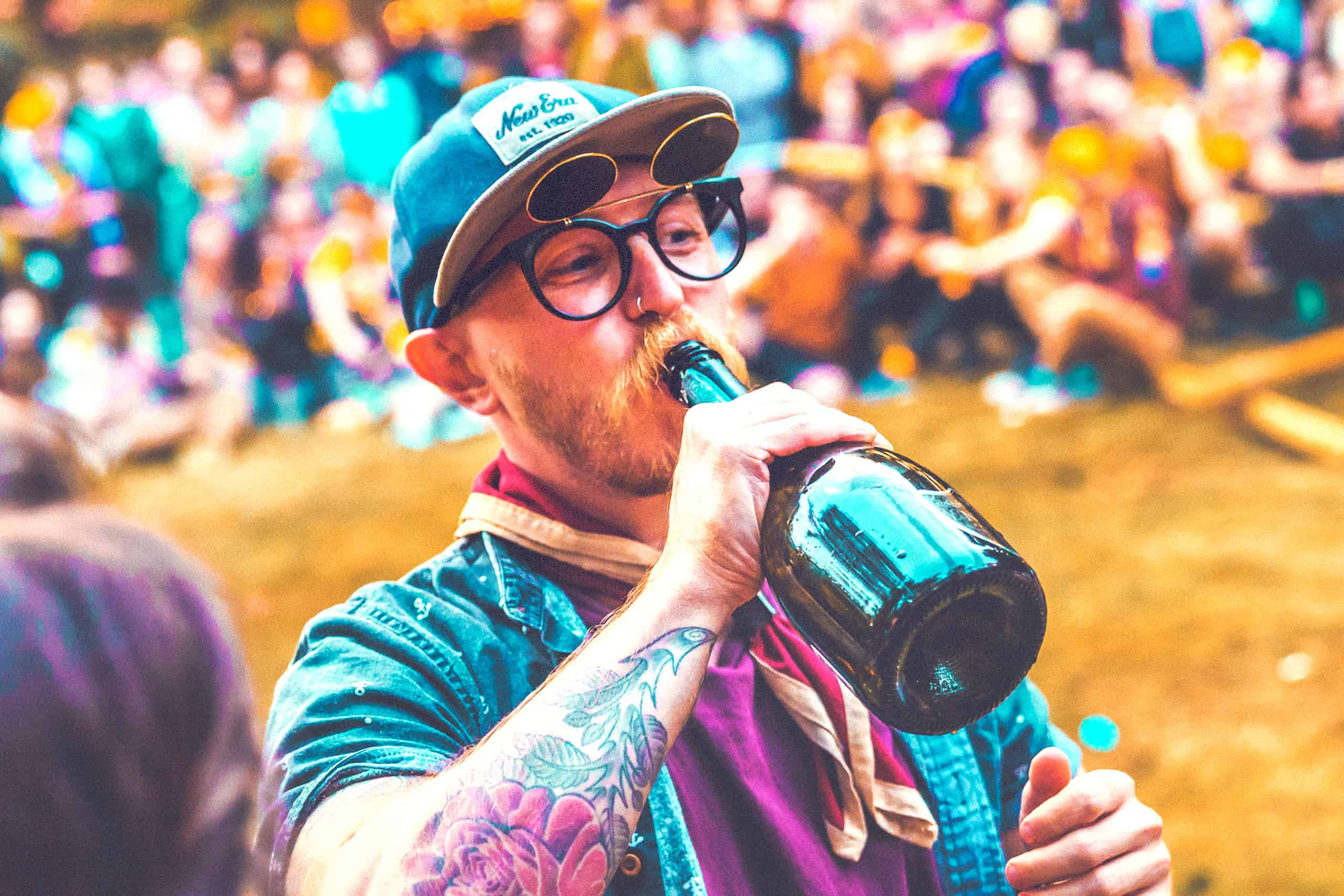 Man drinking from bottle with patrol scarf on at the patrol games at Camp Wildfire. A summer weekend break in a forest near London and Kent. An outdoor woodland retreat featuring adventure activities, live music, DJs, parties and camping. Half summer adventure activity camp, half music festival, for adults only.