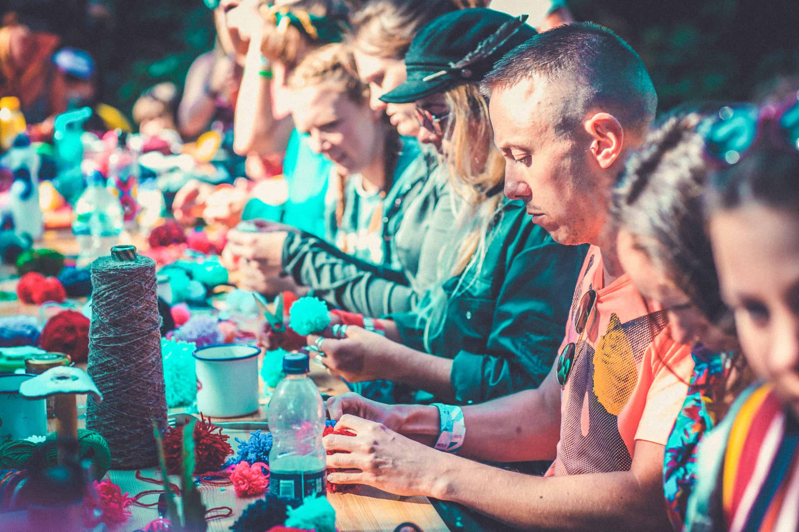 Pom pom making at Camp Wildfire. A summer weekend break in a forest near London and Kent. An outdoor woodland retreat featuring adventure activities, live music, DJs, parties and camping. Half summer adventure activity camp, half music festival, for adults only.