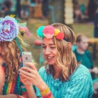 Girl with home made pom pom headband on at Camp Wildfire. A summer weekend break in a forest near London and Kent. An outdoor woodland retreat featuring adventure activities, live music, DJs, parties and camping. Half summer adventure activity camp, half music festival, for adults only.