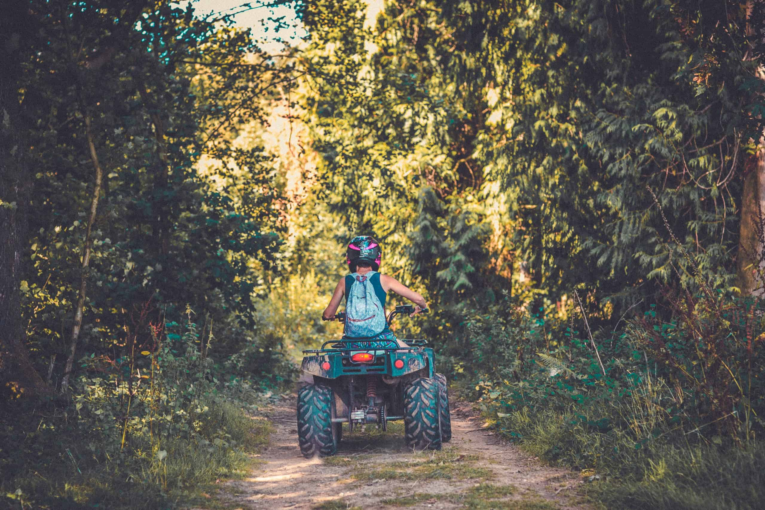 Back of someone on a quad bike at Camp Wildfire. A summer weekend break in a forest near London and Kent. An outdoor woodland retreat featuring adventure activities, live music, DJs, parties and camping. Half summer adventure activity camp, half music festival, for adults only.