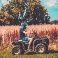 Man on a quad bike at Camp Wildfire. A summer weekend break in a forest near London and Kent. An outdoor woodland retreat featuring adventure activities, live music, DJs, parties and camping. Half summer adventure activity camp, half music festival, for adults only.