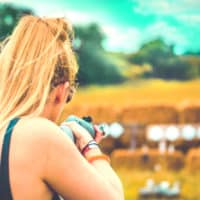 A blonde girl shooting a rifle at Camp Wildfire. The UK's Best Alternative Festival. UK's Top Unique Event. A summer weekend break in a forest near London and Kent. An outdoor woodland retreat featuring adventure activities, live music, DJs, parties and camping. Half summer adventure activity camp, half music festival, for adults only.