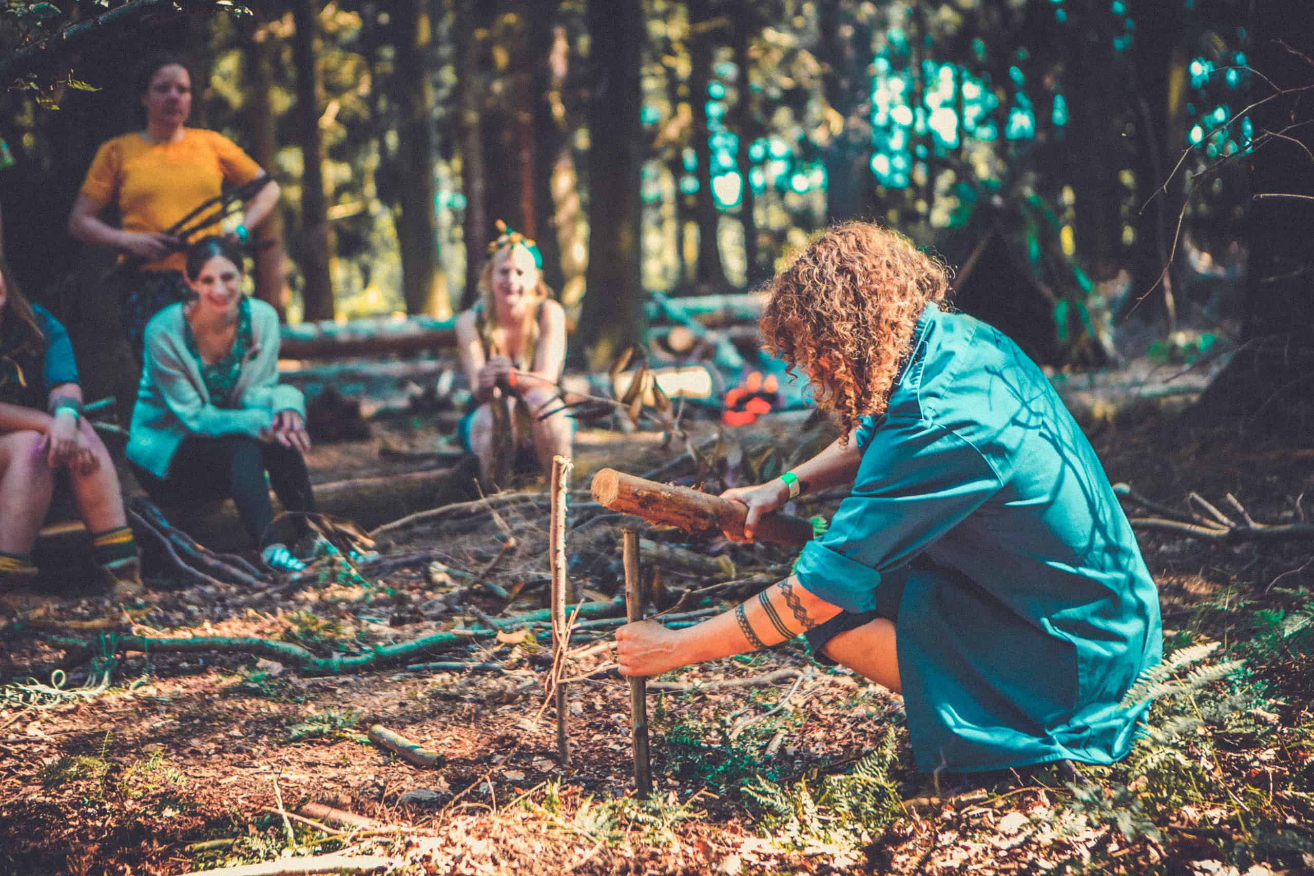 People learning new skills at the shelter building activity at Camp Wildfire. A summer weekend break in a forest near London and Kent. An outdoor woodland retreat featuring adventure activities, live music, DJs, parties and camping. Half summer adventure activity camp, half music festival, for adults only.