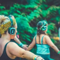 People joining in at the silent disco yoga activity at Camp Wildfire. A summer weekend break in a forest near London and Kent. An outdoor woodland retreat featuring adventure activities, live music, DJs, parties and camping. Half summer adventure activity camp, half music festival, for adults only.